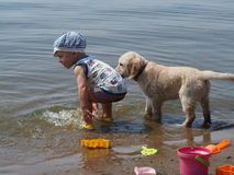 The boy and puppy playing in the river Royalty Free Stock Images