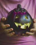 Boy in purple shirt holding big eggplant Jack o Lantern face for Royalty Free Stock Photo