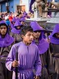 Boy in Easter Procession in Antigua, Guatemala. A boy in purple takes part in Semana Santa (Easter religious processions) in Antigua, Guatemala Royalty Free Stock Image