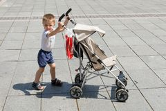 The boy pushes a baby carriage stock images