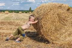 Boy pushes bale of straw Stock Photos