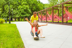 Boy pushes excited girl sitting on skateboard Royalty Free Stock Photo