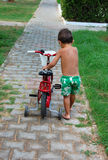 Boy pushing bike Stock Photos