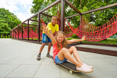 Boy pushing girl sitting on skateboard and roll Stock Images