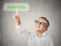 Boy Pushing Kids Only Button. Closeup portrait happy, smiling child touching, pressing Kids only button, icon on touchscreen display isolated grey wall royalty free stock photo