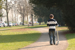 Boy pushing Scooter. Boy walking and pushing scooter down sidewalk stock photo