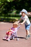 Boy pushing sister in a stroller Stock Photos