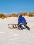 Boy pushing a sledge Royalty Free Stock Image