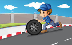 A boy pushing a wheel along the road Stock Photography