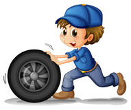 A boy pushing a wheel Stock Images
