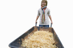 Boy pushing wheelbarrow full of hay, smiling, front view, portrait, cut out Stock Photography