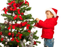 Boy put balls in Xmas tree Royalty Free Stock Photo