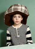 Boy put cat bed as a hat on his head Royalty Free Stock Images