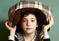 Boy put cat bed as a hat on his head Royalty Free Stock Photos