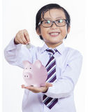 Boy puts the coin into a piggy bank Royalty Free Stock Photography