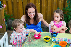 Boy Puts Easter Egg in Pink Dye. A family picture of children painting and decorating eggs.  A mother smiles at her boy as he puts his egg in pink dye at a Royalty Free Stock Images