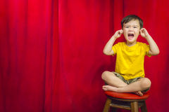 Boy Puts Fingers In Ears on Stool in Front of Theater Curtain Stock Image