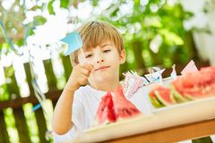 Boy sticks flags as a decoration on watermelons. Boy puts flags as decoration on watermelons at a summer party Stock Image