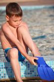 Boy puts on flipperson border of pool Royalty Free Stock Images
