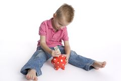 Boy puts money in piggy-bank Royalty Free Stock Photos