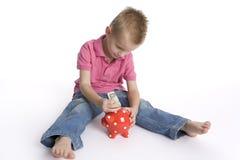 Boy puts money in piggy-bank Royalty Free Stock Photos