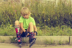 Boy puts rollers. Little boy puts rollers sitting on the roadside Royalty Free Stock Image