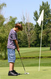 Boy Putting. Boy golfer putting on the green Royalty Free Stock Photos