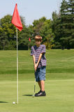 Boy Putting. Boy golfer putting on the green Royalty Free Stock Image