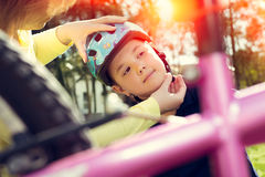 Boy putting on a bike helmet Royalty Free Stock Image