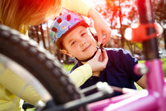 Boy putting on a bike helmet Royalty Free Stock Photos