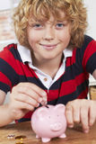 Boy Putting Coins Into Piggy Bank Stock Images
