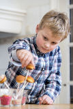 Boy putting cupcake pop in glass Stock Photos