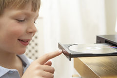 Boy Putting Disc In DVD Royalty Free Stock Images