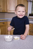 Boy putting icing on cookie Royalty Free Stock Photography