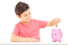 Boy putting money into a piggybank Stock Image