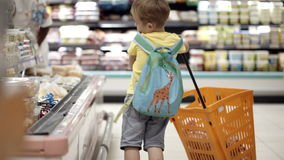 Boy putting products into shopping cart stock video footage