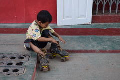 Boy putting on rollerskates Stock Photo