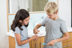 Boy putting toothpaste on sister toothbrush in bathroom. At home Royalty Free Stock Photo