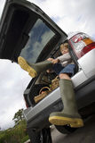 Boy (8-10) putting on wellington boots, sitting in boot of stationary car, smiling, portrait, low angle view (tilt).  Royalty Free Stock Image