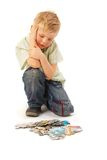 Boy with puzzles. Thinking... Stock Photography