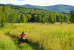 Boy on Quad. Boy riding quad ATV 4 wheeler on trail through tall grass open field in the Catskill Mountains, NY Royalty Free Stock Photo