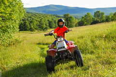 Boy on Quad. Boy riding quad ATV 4 wheeler on trail through tall grass open field in the Catskill Mountains, NY Stock Photography