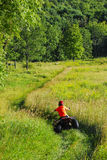 Boy on Quad. Boy riding quad ATV 4 wheeler on trail through tall grass open field in the Catskill Mountains, NY Royalty Free Stock Images