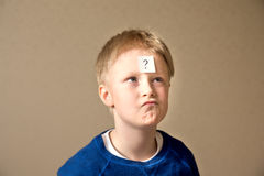 Boy with question mark. Thinking confused young boy (teen) with question mark on gray background Stock Photos