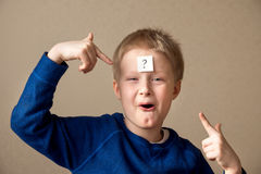 Boy with question mark. Thinking young boy with question mark on gray background Royalty Free Stock Photography