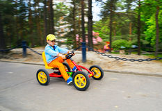 The boy quickly riding a four-wheeled bike in  Park . Royalty Free Stock Photography