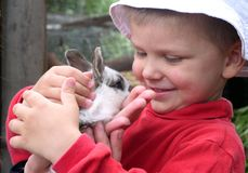 Boy and Rabbit. A boy holding a rabbit in his hands stock photography