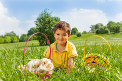 Boy with rabbit and two baskets in the park Stock Photo