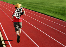 Boy on a racetrack. Boy with a checkered flag running on a racetrack Royalty Free Stock Photography