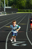 Boy Racing on Track. Boy smiling racing someone on race track Royalty Free Stock Images